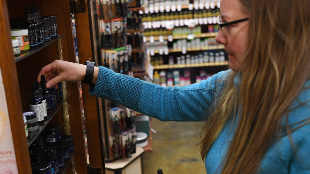 a woman in a shop and leaning into a cabinet with Hemp seed oil and CBD oil