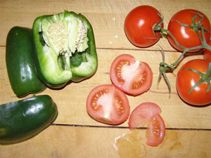 Green peppers and red tomatoes on brown table cut open to show their seeds