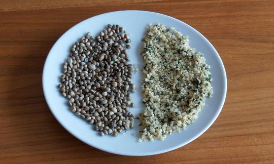 The photo shows a plate with unshelled hemp seeds (left) and shelled hemp seeds (right).